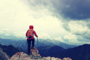 successful woman backpacker enjoy the view on mountain peak